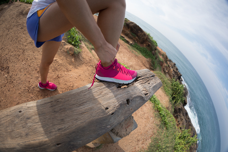 Trail runner tying shoelace ready for running at seaside