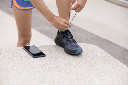 Healthy lifestyle woman runner tying shoelace on city