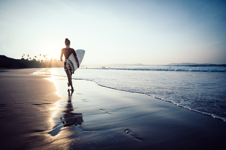 Surfer woman walking with surfboard on sunrise beach