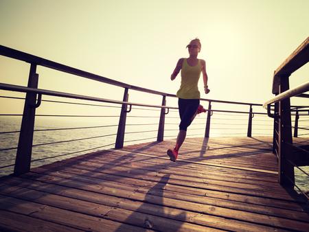 weiblicher Läufer der sportlichen Fitness, der während des Sonnenaufgangs auf Strandpromenade läuft