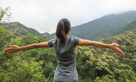 young woman feel free at forest mountain top
