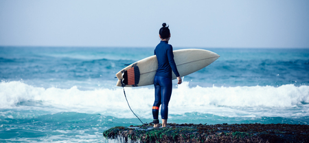 Woman surfer with surfboard going to surf 스톡 콘텐츠