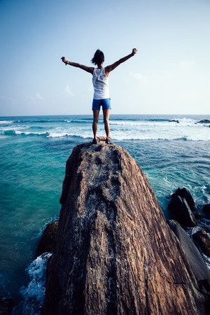 Successful woman outstretched arms on seaside rock cliff edge Imagens