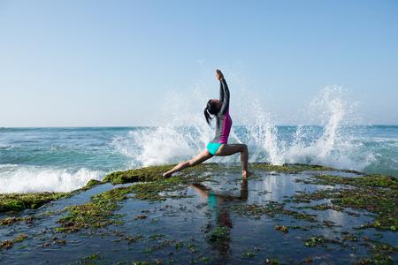 Mujer practica yoga en el borde del acantilado de coral junto al mar Foto de archivo