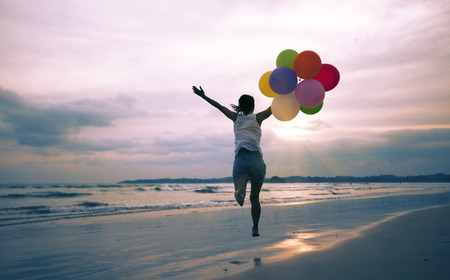 young asian woman running and jumping on seaside with colored balloons Archivio Fotografico