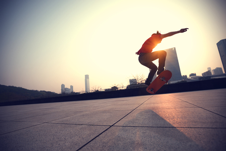 Skateboarder skateboarding at sunrise city 版權商用圖片