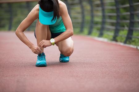 Runner athlete tying shoelace on spring forest trail. woman fitness jogging workout wellness concept. Reklamní fotografie