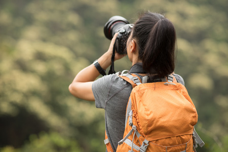 woman photographer taking photo on morning mountain forest Reklamní fotografie