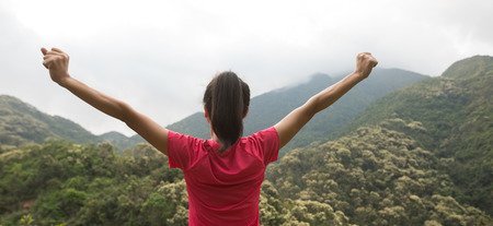 young woman  feel strong at forest mountain top
