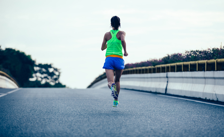 Young fitness woman running on city road