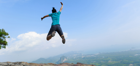 successful woman jumping on rocky mountain peak