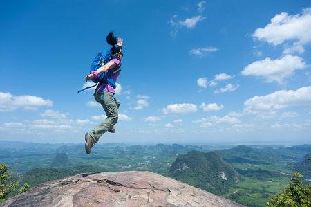 Happy successful woman hiker jumping on mountain peak cliff edge