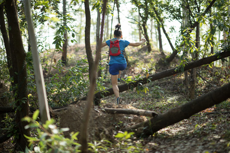 Sportswoman cross country trail running in tropical autumn forest