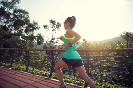 Runner athlete running on spring forest trail. woman fitness jogging workout wellness concept. Stockfoto