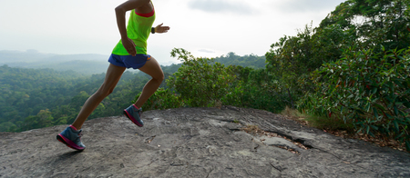 young asian woman runner running on  sunset mountain peak