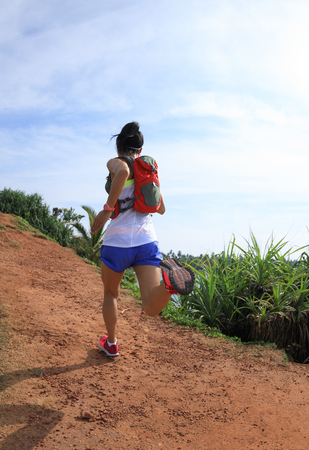 Woman trail runner running on seaside hills