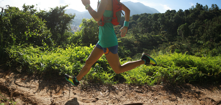 Young fitness woman trail runner running in summer forest
