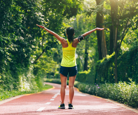 Healthy lifestyle woman runner raised arms in morning park Imagens