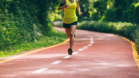 Gesunder Lebensstilfrauenläufer, der auf Morgenparkstraße läuft Standard-Bild