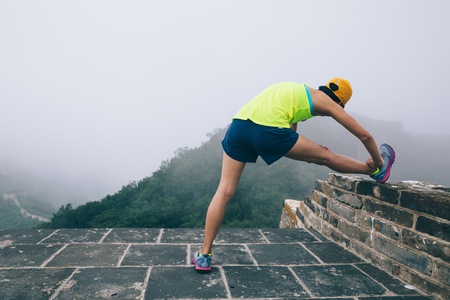 sporty fitness woman trail runner running up to the top of great wall on mountain