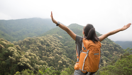 young woman backpacker hiking at forest mountain top Imagens