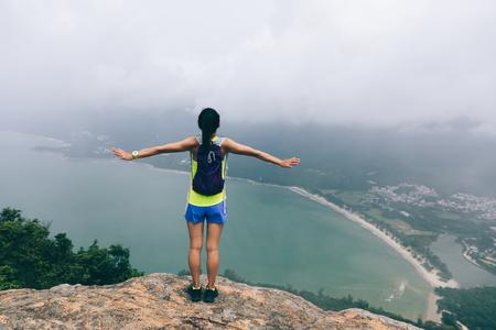 Exitosa mujer excursionista siéntase libre en la cima de la montaña junto al mar