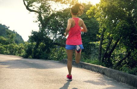 Giovane donna sportiva in trail running di abbigliamento sportivo sul sentiero di montagna della foresta. Ragazza fitness che fa jogging a Hong Kong