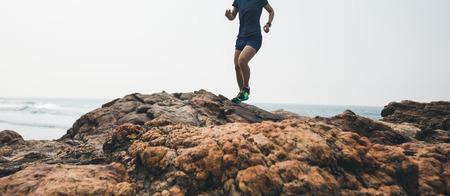 Donna trail runner che corre verso la cima di una montagna rocciosa in riva al mare