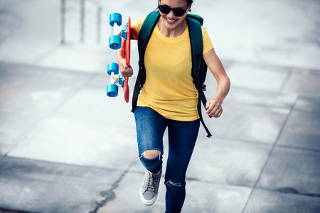 Woman skateboarder walking with skateboard in hand at city stairs Stock Photo