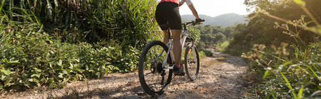 Woman cyclist riding a bike on a nature trail in the mountains. People living a healthy lifestyle Foto de archivo