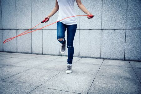 Young fitness woman rope skipping at city
