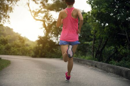 Sporty young woman in sportswear trail running on forest mountain path. Fitness girl jogging in Hong Kong Stock Photo