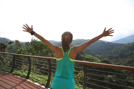 Woman runner outstretched arms on spring morning