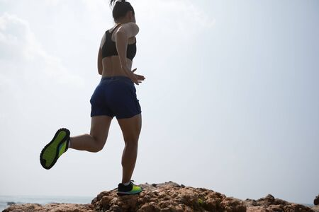 Woman ultramarathon trail runner running to rocky mountain top on seaside 版權商用圖片