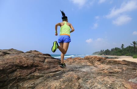 Woman ultramarathon trail runner running to rocky mountain top on seaside