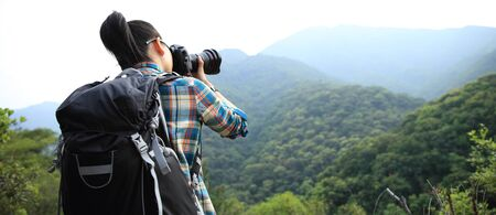 Woman photographer taking photo on morning mountain forest
