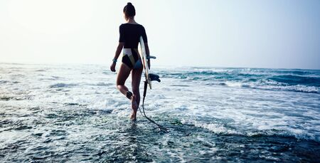 Woman going to surf with surfboard
