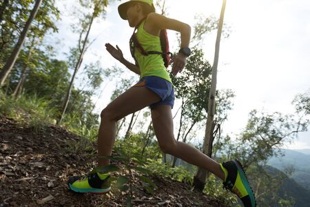 Sportswoman cross country ultra marathon trail runner running in forest