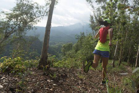 Sportswoman cross country ultra marathon trail runner running in forest