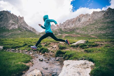 Woman ultra marathon trail runner jumping over small river on beautiful mountains Banco de Imagens