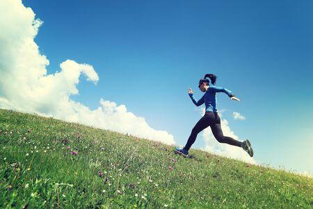 Woman ultramarathon trail runner running up on grassland mountain Imagens