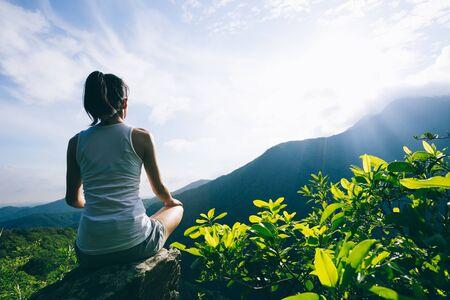 Yoga woman meditating on mountain peak cliff edge in the sunrise