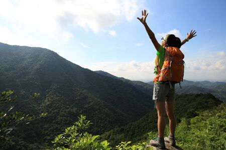 Cheering young woman backpacker enjoy the view at summer mountain peak Banco de Imagens