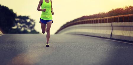 Young fitness asian woman runner running on city road Imagens