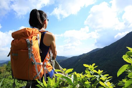 Young woman backpacker enjoy the view at summer mountain peak