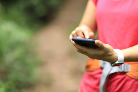 Woman hiker using smartphone on hiking travel