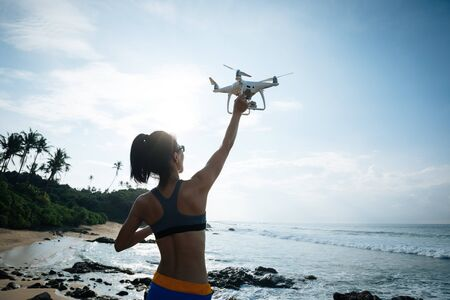 Woman landingtaking off drone which taking photo over sea