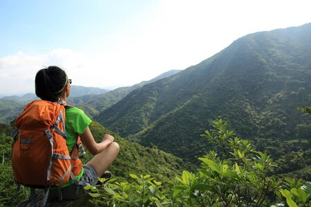 Successful young woman backpacker enjoy the view on spring forest mountain cliff edge Banco de Imagens
