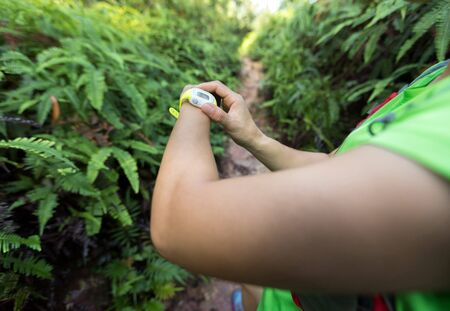 Asian woman ultra marathon runner set the sports watch before trail running on mountain
