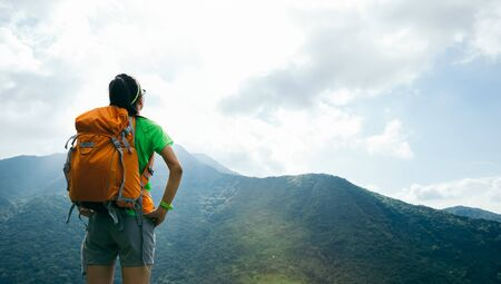 Successful woman backpacker enjoy the view on summer mountain peak